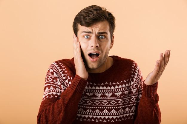 Homem confuso com a barba por fazer, vestindo um suéter de tricô, gritando e tocando o rosto, isolado sobre uma parede bege