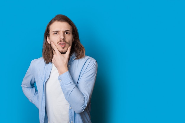Homem confuso com cabelo comprido e cerdas tocando o queixo com a mão posando em roupas casuais em um azul
