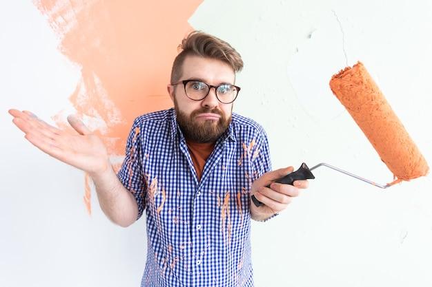Homem confuso com rolo de pintura dentro de casa. redecoração, renovação, reparação de apartamentos.