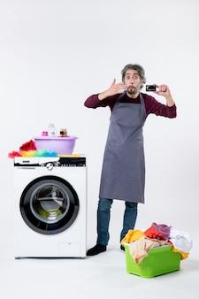 Homem confuso de vista frontal segurando um cartão em pé perto da máquina de lavar roupa em fundo branco