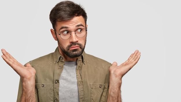 Homem confuso e atraente com a barba por fazer encolhe os ombros, olha com hesitação de lado, franze os lábios em perplexidade, tem uma expressão sem noção
