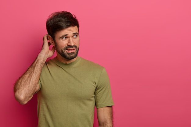 Homem confuso e indignado coça a cabeça e tenta decidir algo