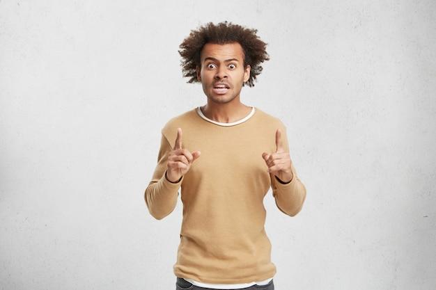 Homem confuso e irritado olha para a câmera e abre a boca amplamente, levanta os dedos da frente e fica em choque