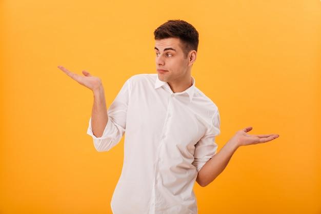 Homem confuso na camisa branca encolhe os ombros e desviar o olhar
