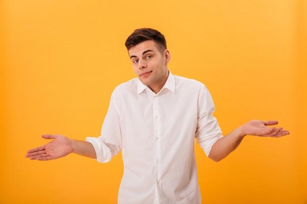 Homem confuso na camisa branca encolhe os ombros e olhando para a câmera