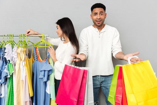 Homem confuso segurando sacolas de compras enquanto mulher escolhendo roupas