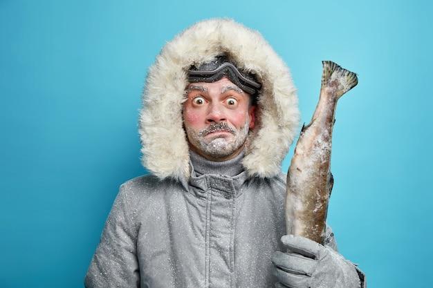 Homem congelado surpreso perplexo passa longas horas ao ar livre durante um dia frio severo vestido com uma jaqueta de inverno cinza e luvas segurando peixe usa óculos de esqui.