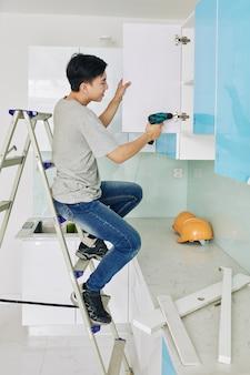 Homem consertando a porta do armário