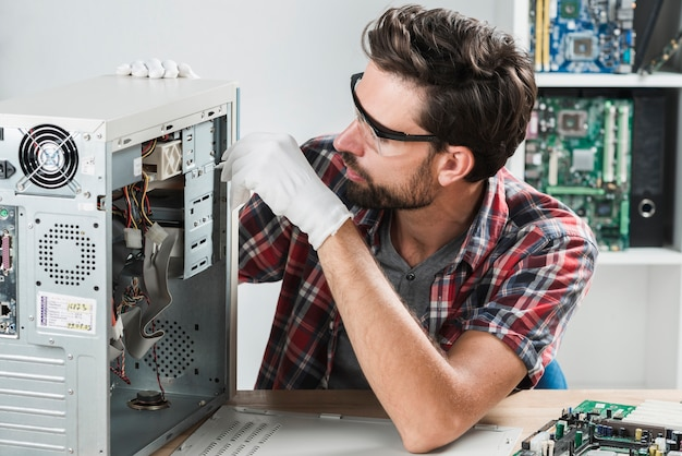 Homem consertando cpu com chave de fenda na oficina