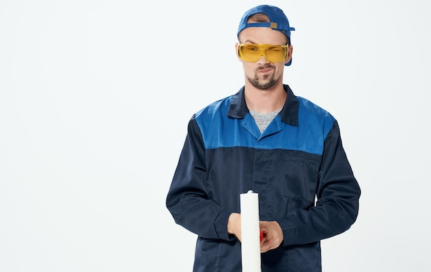 Homem consertando terno azul de rolo de pintura e óculos com boné