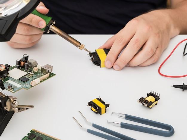 Homem consertando um conector usando o ferro de solda