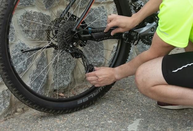 Homem consertando uma bicicleta durante um passeio de bicicleta