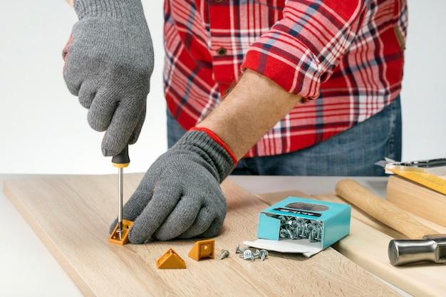 Homem consertando uma peça de mobília a bordo em casa com uma chave de fenda. homem caucasiano, montagem de móveis. faça você mesmo a montagem dos móveis.