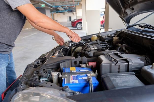 Homem consertar um carro.
