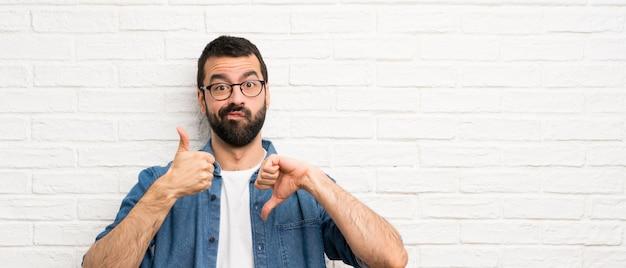 Homem considerável com a barba sobre a parede de tijolo branca que faz o sinal bom-mau. indeciso entre sim ou não