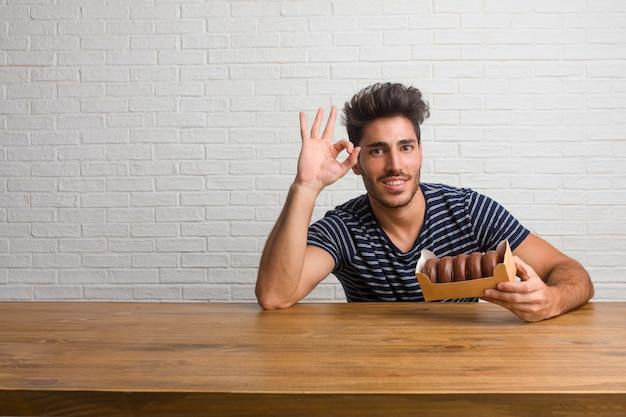 Homem considerável e natural novo que senta-se em uma tabela alegre e seguro fazendo o gesto aprovado, entusiasmado e gritando, conceito da aprovação e sucesso. comendo rosquinhas de chocolate.