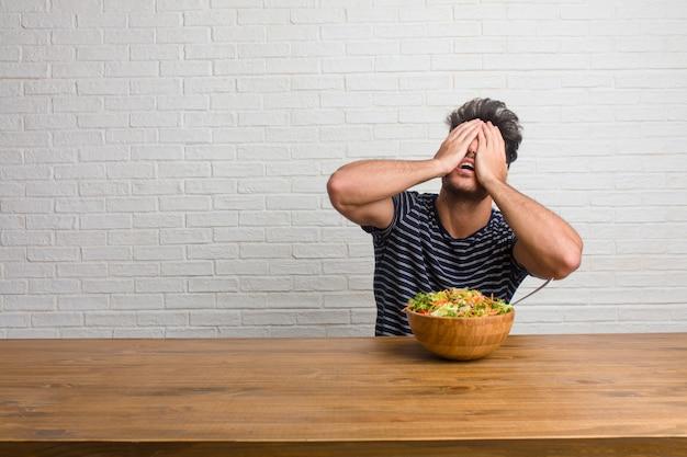 Homem considerável e natural novo que senta-se em uma tabela frustrada e desesperada, irritada e triste com mãos na cabeça. comendo uma salada fresca.