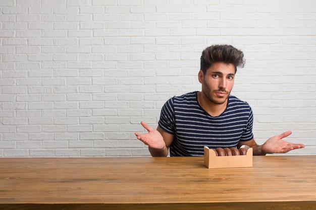 Homem considerável e natural novo que senta-se em uma tabela que duvida e que encolhe ombros