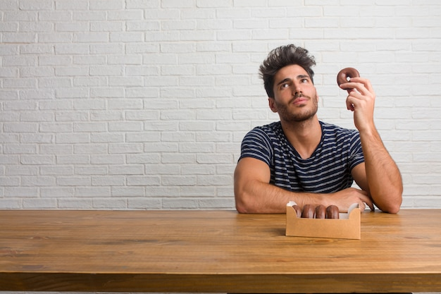 Homem considerável e natural novo que senta-se em uma tabela que olha acima