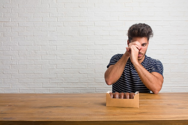 Homem considerável e natural novo que senta-se em uma tabela que olha com uma diferença