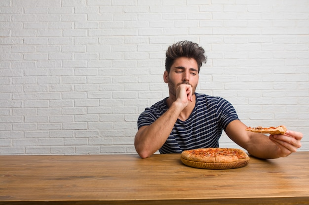 Homem considerável e natural novo que senta-se em uma tabela que pensa e que olha acima