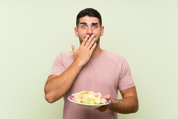 Homem considerável novo com salada sobre a parede verde isolada com expressão facial da surpresa
