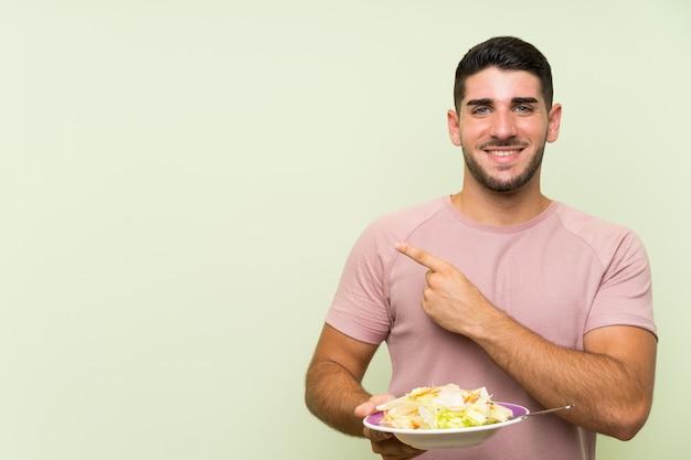 Homem considerável novo com salada sobre a parede verde isolada que aponta ao lado para apresentar um produto