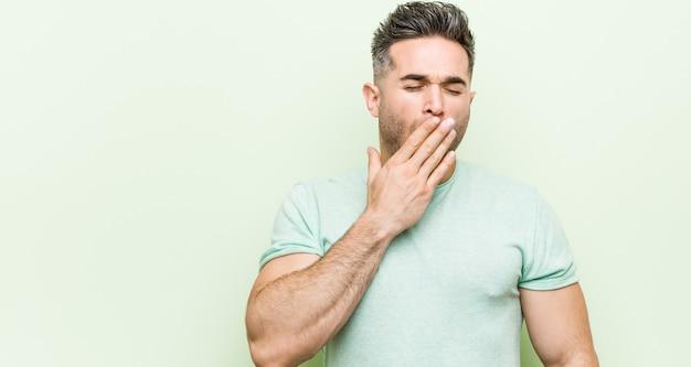 Homem considerável novo contra um fundo verde que boceja mostrando um gesto cansado que cobre a boca com a mão.