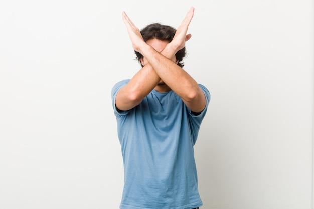 Homem considerável novo no branco que mantém dois braços cruzados, conceito da negação.