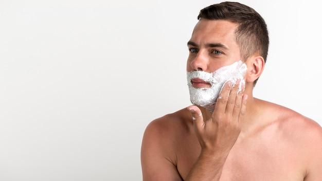 Homem considerável novo que aplica o creme de rapagem que está contra a parede branca