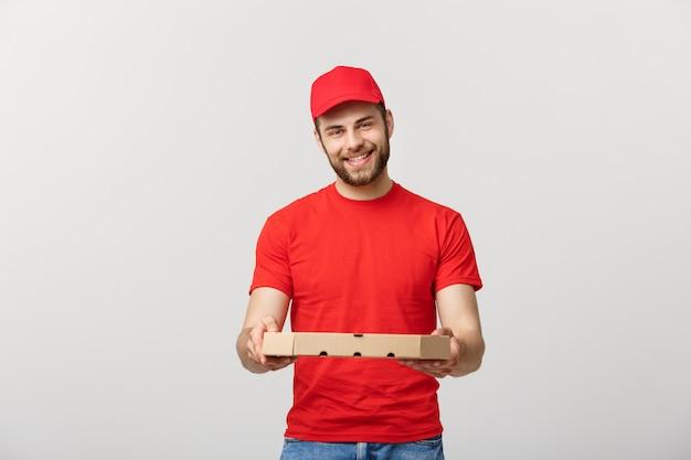 Homem considerável novo que entrega a pizza isolada sobre o fundo cinzento.
