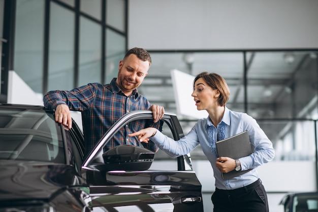 Homem considerável novo que escolhe um carro em uma sala de exposições do carro