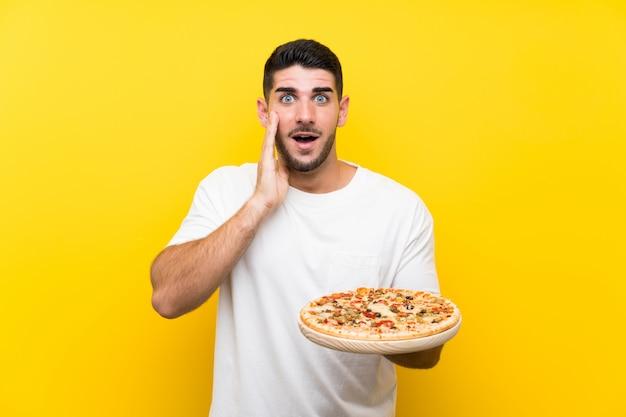 Homem considerável novo que guarda uma pizza na parede amarela com surpresa e expressão facial chocada