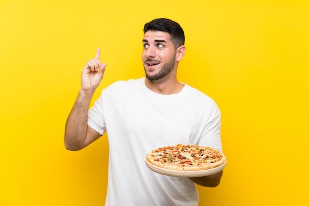 Homem considerável novo que guarda uma pizza sobre a parede amarela isolada que pretende realizar a solução ao levantar um dedo acima