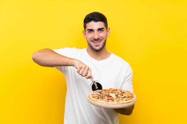 Homem considerável novo que guarda uma pizza sobre a parede amarela isolada