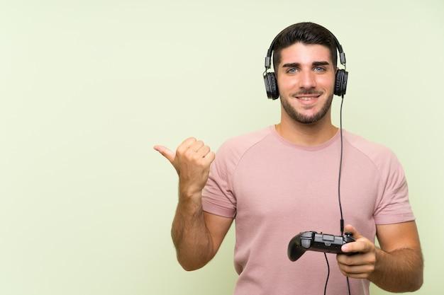 Homem considerável novo que joga com um controlador do jogo video sobre a parede verde isolada