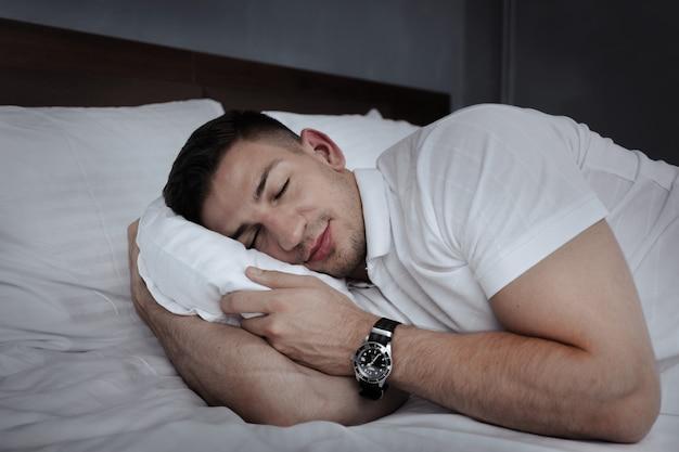 Homem considerável novo que relaxa na cama após um dia difícil no trabalho
