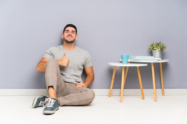 Homem considerável novo que senta-se no assoalho que dá os polegares acima do gesto