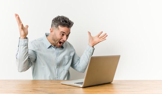 Homem considerável novo que trabalha com seu portátil que comemora uma vitória ou um sucesso, é surpreendido e chocado.