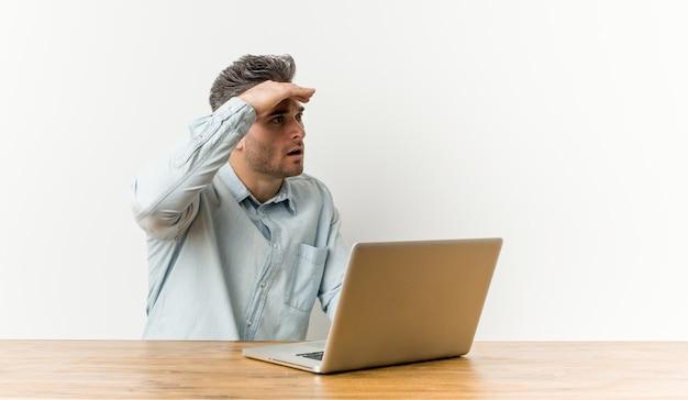 Homem considerável novo que trabalha com seu portátil que olha longe de manter a mão na testa.