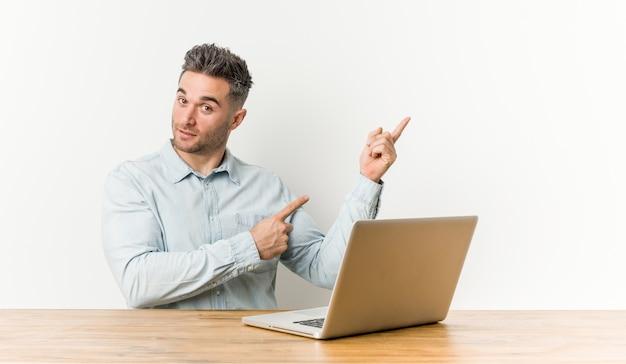 Homem considerável novo que trabalha com seu portátil que sorri alegremente apontando com dedo indicador afastado.