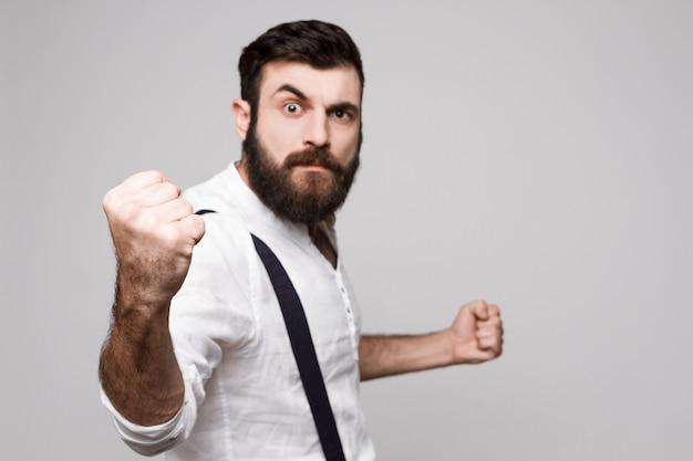 Homem considerável novo rude irritado que mostra o punho sobre o branco.