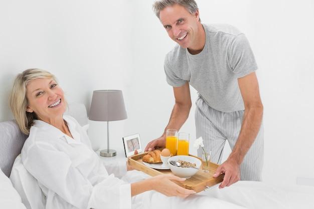 Homem considerável que dá café da manhã na cama ao parceiro