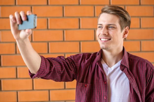 Homem considerável que faz o selfie na parede de tijolo.