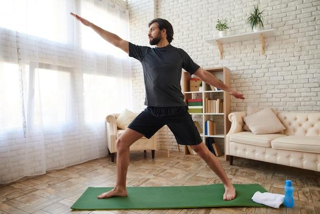 Homem considerável que pratica ioga avançada em casa.