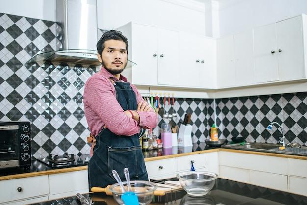 Homem considerável que prepara o material para cozinhar em casa.