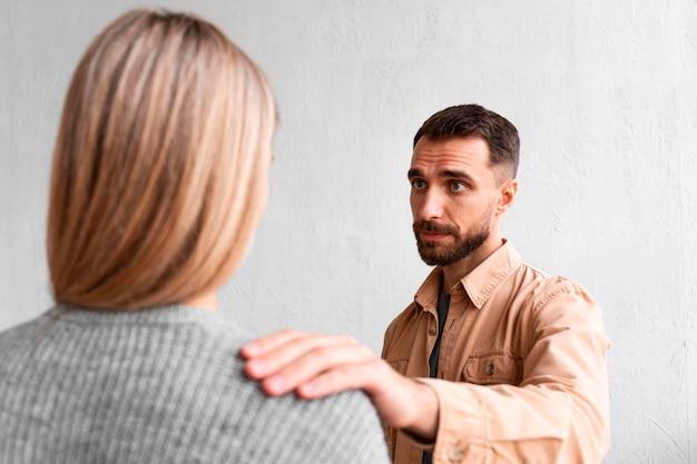 Homem consolando mulher em sessão de terapia em grupo