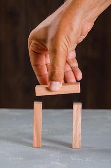 Homem construindo arco de blocos de madeira.