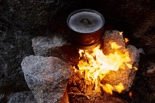 Homem construiu uma fogueira na floresta na natureza, sobreviver