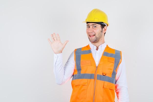 Homem construtor acenando com a mão para saudação na camisa, uniforme e olhando alegre, vista frontal.